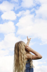 Side view of girl pointing towards sky - CAVF45935