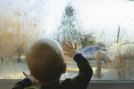 Rear view of boy looking through condensed glass window - CAVF45968