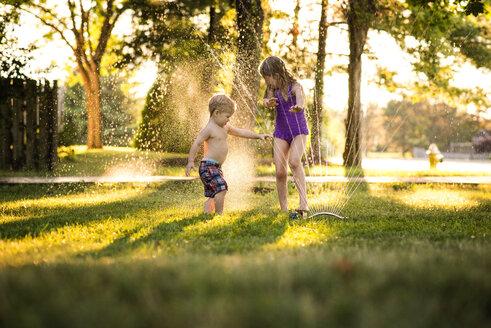 Cheerful siblings playing in sprinkler - CAVF45998