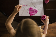 High angle view of girl coloring heart shapes on table at home - CAVF46040