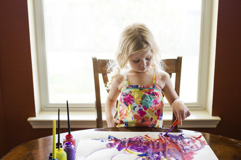 Girl coloring paper against window at home - CAVF46058