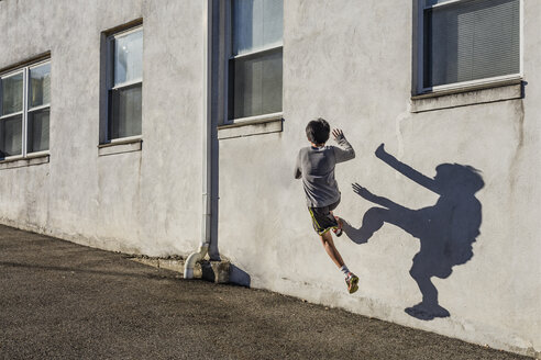 Rear view of teenage boy jumping over wall during sunny day - CAVF46073