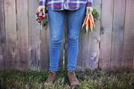 Low section of female farmer holding vegetables while standing against fence at organic farm - CAVF46205