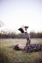 Young woman holding hat while relaxing on grassy field - CAVF46220