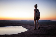 Rear view of woman walking by pond on field during sunset - CAVF46241