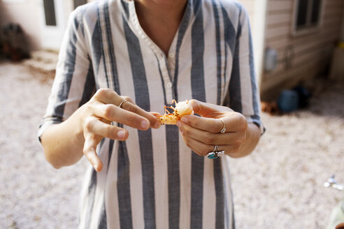 Midsection of woman holding prawn while standing in yard - CAVF46292