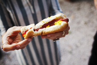 Close-up of woman holding hot dog - CAVF46304