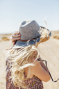 Woman in sun hat standing against at desert against clear sky during sunny day - CAVF46382