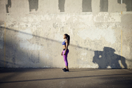 Side view of sportswoman standing on street by wall - CAVF46502
