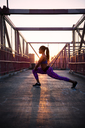 Woman stretching while exercising on metallic bridge during sunny day - CAVF46520