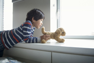 Boy playing with stuffed toy on window sill at home - CAVF46571