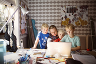 Mother and sons using laptop on messy table against wall at home - CAVF46598