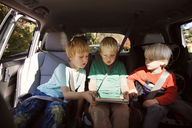 Brothers looking at tablet computer while sitting in car - CAVF46601