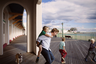 Playful family on boardwalk outside building against cloudy sky - CAVF46604