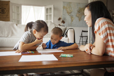 Mother looking at children drawing on table in living room - CAVF46709