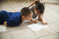 Brother looking at sister drawing on paper while lying on floor in living room - CAVF46712
