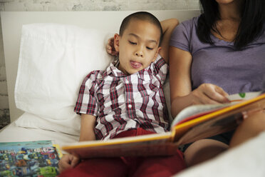 Boy listening to mother reading book on bed at home - CAVF46715