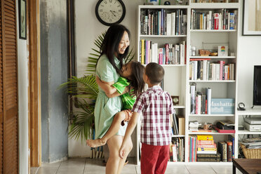 Happy mother carrying daughter while looking at son in living room - CAVF46724