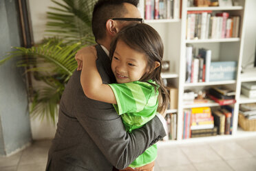 Smiling daughter embracing father while standing in living room at home - CAVF46733