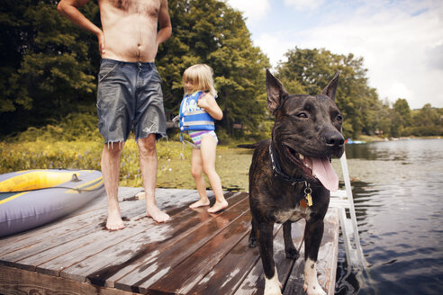 Grandfather and granddaughter with dog standing on pier - CAVF46889