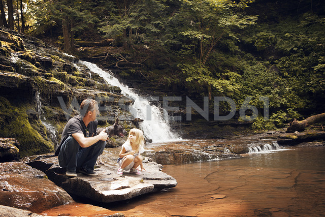 Grandfather and granddaughter with dog crouching on rocks at lakeshore - CAVF46892 - Cavan Images/Westend61