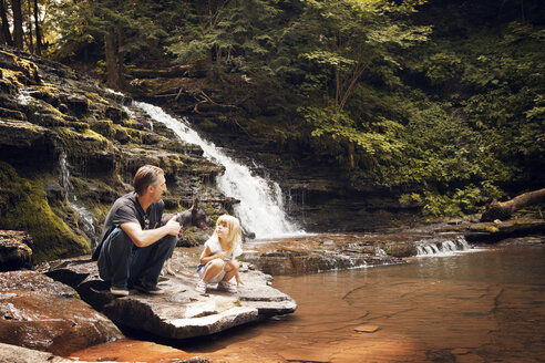 Grandfather and granddaughter with dog crouching on rocks at lakeshore - CAVF46892