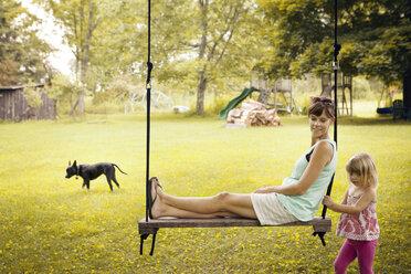 Girl swinging grandmother at park - CAVF46895