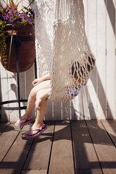 Girl relaxing on hammock at yard - CAVF46904