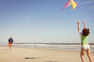 Grandfather and granddaughter playing with kite on sand at beach - CAVF46931
