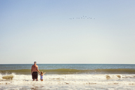 Grandfather and grandson standing in sea - CAVF46940