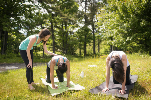 Trainer assisting women for practicing downward facing dog position field - CAVF46979