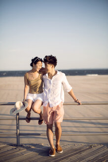 Smiling couple by railing at pier against clear sky - CAVF47003