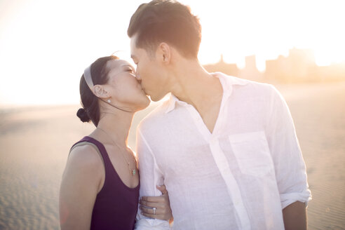 Affectionate couple kissing while standing at beach - CAVF47006