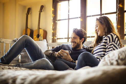 Happy couple having coffee while resting on alcove window seat at home - CAVF47032