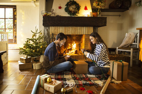 Couple wrapping gift boxes on floor by fireplace at home - CAVF47062