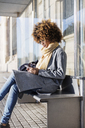 Woman using mobile phone while sitting on seat at bus stop - CAVF47089