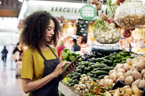 Vendor using tablet computer at market stall - CAVF47122