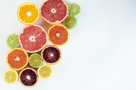 Overhead view of various chopped citrus fruits on paper - CAVF47278