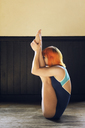 Side view of woman exercising yoga at home - CAVF47281