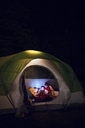 Friends looking at digital tablet while relaxing in tent - CAVF47296