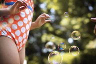 Midsection of girl playing with bubbles outdoors - CAVF47299