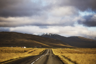 Country road leading towards mountains against cloudy sky - CAVF47347