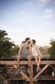 Affectionate farming couple kissing while sitting on wooden structure at farm against sky - CAVF47449