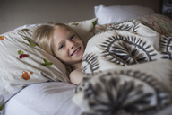 Portrait of happy boy lying in bed - CAVF47458