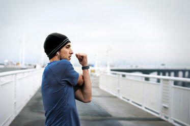 Side view of determined male athlete exercising on Bay Bridge against clear sky - CAVF47473