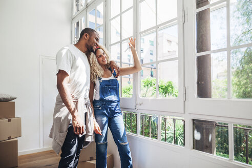 Smiling couple looking at keys while standing by window at home - CAVF47563
