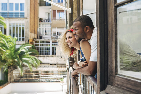 Happy couple looking through window while standing at home - CAVF47584