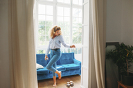 Full length of young woman dancing while listening music through smart phone at home - CAVF47593