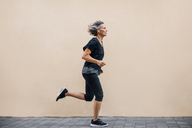 Side view of woman jogging on footpath against wall - CAVF47635