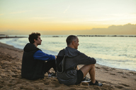Thoughtful father and son resting while sitting t beach against sky during sunset - CAVF47731